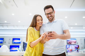 Close up of focused smiling couple in love choosing and holding a mobile in a tech store.