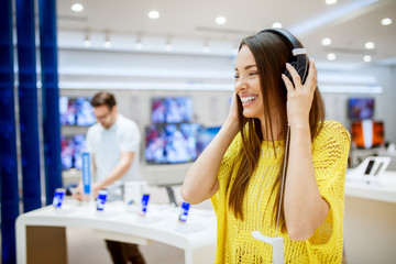 Self adhesive Wall Murals Music store Close up of adorable attractive happy girl testing headphones in a tech store.