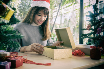 woman wearing santa hat packaging gift box