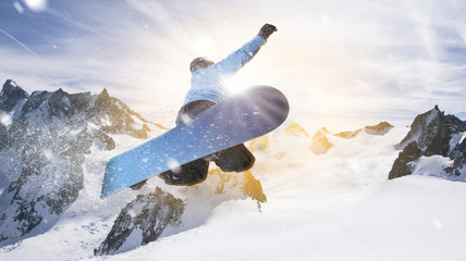 snowboarder jumps through the air into the sunlight