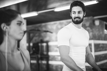 Handsome muscular bearded sportive man looking in the girl next to him while practicing on the treadmill in the gym. Black and white photo.
