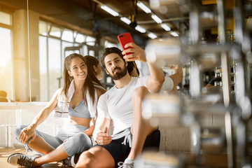 Young attractive smiling active fitness couple sitting on the floor of the gym and taking a selfie, leaning on the mirror with a towel.