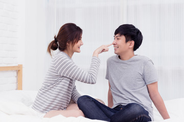 Cute asian couple sitting on the bed. Joyful, happy and funny lover. Lover concept.