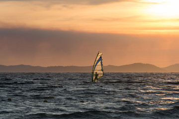 Sunset over the sea or ocean and extreme freestyle sport windsurfing