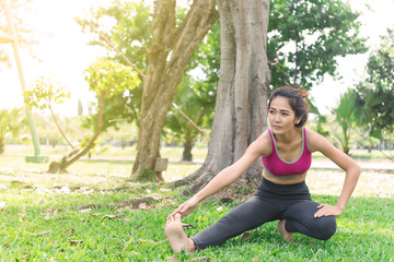 Asian slim woman warm up before work out in a morning,slim girl exercise for life,selective focus,fill bright sunlight,Thailand people