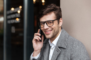 Smiling business man in eyeglasses and coat talking by smartphone