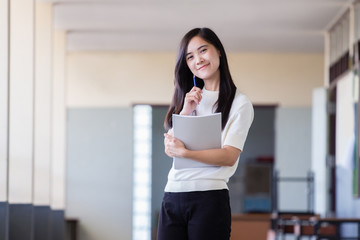 Asian woman holding book inside school hall way with blurry background