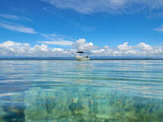 Seascape seen from calm water surface a boat with cloudy blue sky, Bocas del Toro, Caribbean sea, Panama, Central America