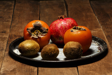 Persimmon, kiwi, pomegranate on a platter on a wooden table.