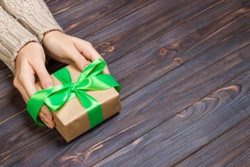 Woman's hands give wrapped valentine holiday handmade present in craft paper with green ribbon. Present box, decoration of gift on black wooden table, POV with copy space