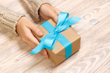Woman's hands give wrapped valentine holiday handmade present in craft paper with blue ribbon. Present box, decoration of gift on black wooden table, POV with copy space