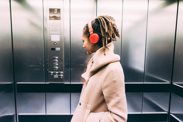 young woman outdoor listening music elevator