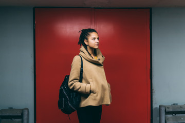 Thoughtful young woman standing against door