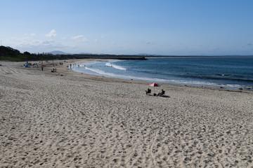 Badestrand mit Sonnenschirm und zwei Personen im rechten Drittel und viel Sand im vorderen Bereich