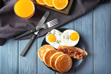 Plate with yummy pancakes, fried bacon and eggs on wooden table