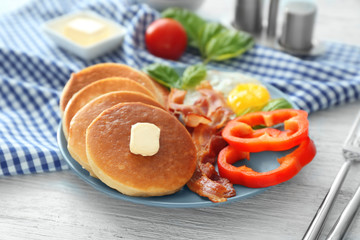 Plate with yummy pancakes, pepper, fried egg and bacon on wooden table