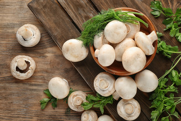 Fresh champignon mushrooms on wooden table