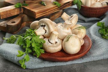 Fresh champignon mushrooms on wooden plate