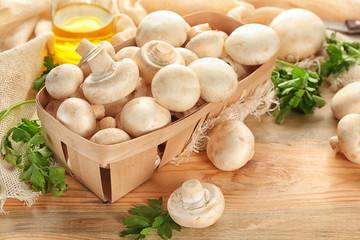 Basket with fresh champignon mushrooms on table