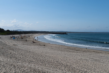 Badenstrand mit weitläufiger Sandfläche im Vordergrund und Badegästen im hinteren Bildteil