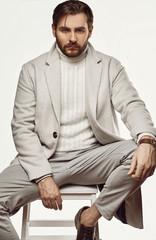 Brutal elegant man in gray coat isolated on white background
