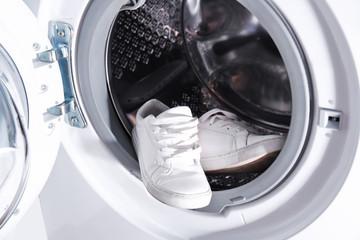 Pair of white sneakers in washing machine, closeup