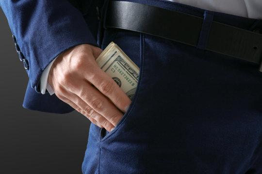 Man in formal suit putting money in pocket on dark background, closeup