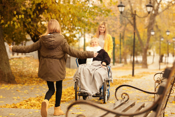 Elderly woman in wheelchair with her family outdoors on autumn day