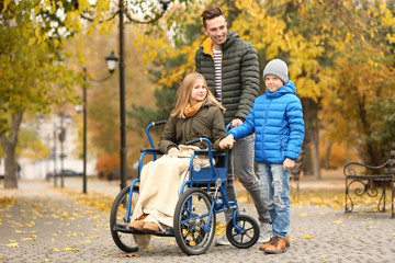 Teenage girl in wheelchair with her family outdoors on autumn day