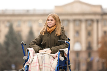 Teenage girl in wheelchair outdoors on autumn day