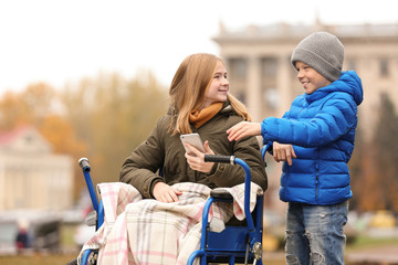 Teenage girl in wheelchair with her brother outdoors on autumn day