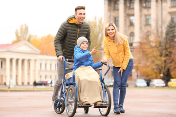 Couple with their little son in wheelchair outdoors on autumn day