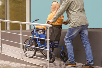 Man with his wife in wheelchair on ramp outdoors