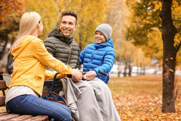 Man in wheelchair with his family outdoors on autumn day