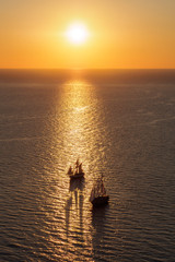 two boats on the sea surface at sunrise