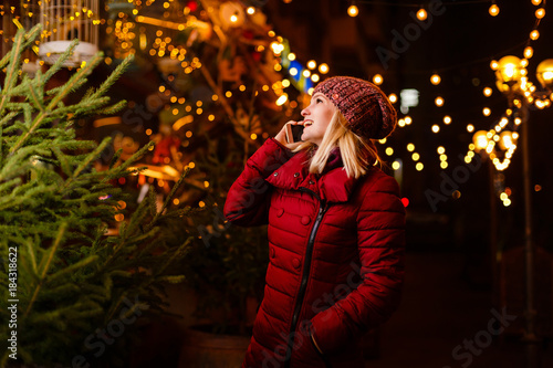 happy woman is buying a christmas tree on the street with christmas light at night