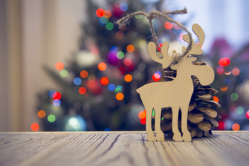 A wooden table with a plain wooden toy moose on the right against decorated Christmas tree with colorful fairy lights. Blurred bokeh background. Close up. Mock up for display of product