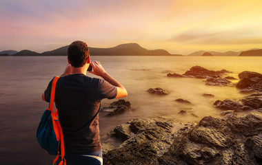 Man using smartphone shooting image on sea sunset or sunrise in twilight