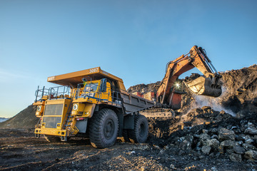 Big yellow dump truck and excavator in the coal mine, fisheye