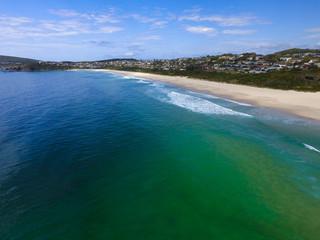 Luftbild mit Blick auf einen Sand-Badestrand mit interessantem Farbenspiel des Meer