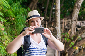 portrait of a tourist in a hat with a phone for a photo