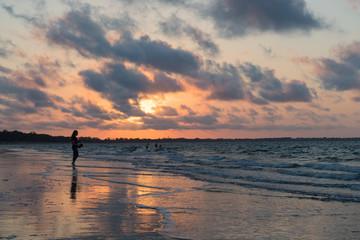 Einzelne Frau beim Spaziergang am Strand während Sonnenuntergang blickt aufs Meer