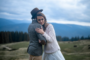 Bride and groom stand and hug on background of Carpathians mountains.