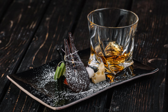 Whiskey and appetizer on black plate on dark wood background