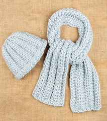Woolen scarf and cap isolated on linen background.