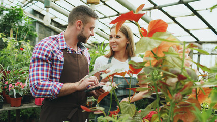 Young couple florists work in garden center. Attractive man and woman in apron count flowers using tablet computer during working in greenhouse