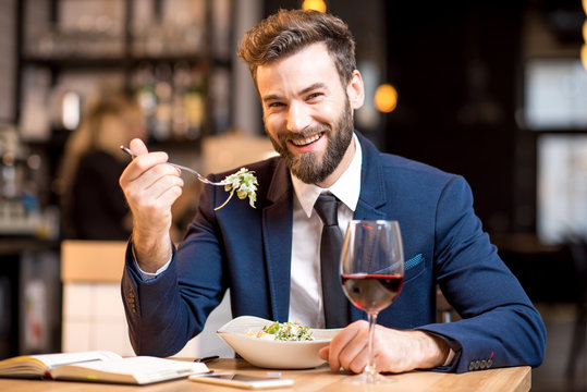 Elegant businessman dressed in the suit having a dinner with salad and wine sitting at the modern restaurant interior