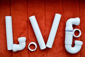 The inscription love is made up of white, plumbing, plastic pipes, fittings, flanges, rubber gaskets on the background of a red carpet. A word of love written by water pipes.