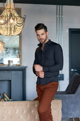 Sexy man model in dark shirt at luxury interior