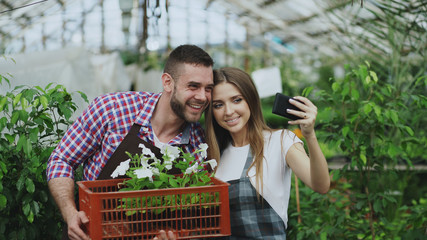 Cheerful loving couple gardeners taking selfie picture on smartphone camera while working in greenhouse